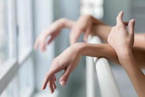 les mains de deux danseurs de ballet classiques à la barre photo