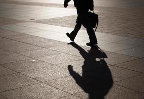 homme marchant pour travailler tout en portant une mallette photo