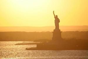Statue de la liberté à new york au coucher du soleil