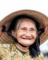 vieille femme sympathique avec chapeau de paille vietnamien photo