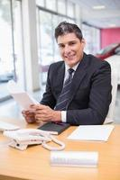vendeur souriant tenant un document photo