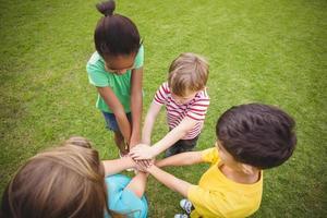 camarades de classe divers mettant les mains ensemble photo