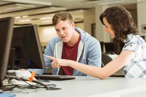 camarades de classe travaillant ensemble dans la salle informatique photo