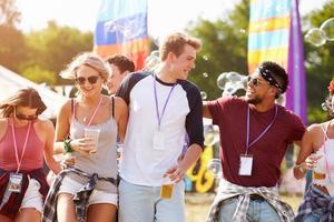 amis marchant ensemble à travers un site de festival de musique photo