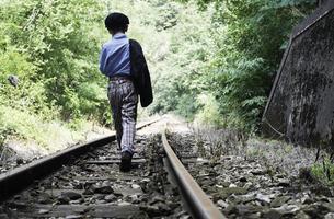 enfant marchant sur le chemin de fer photo