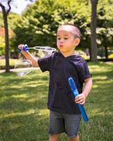 jeune enfant jouant avec des bulles photo