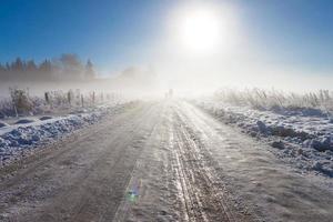 mère et enfant sur route de neige brumeuse