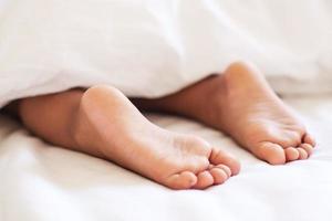 pieds d'enfant sous la couverture. photo