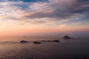 vue sur l'océan au lever du soleil avec des îles à l'horizon