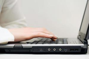mains féminines à l'aide d'un ordinateur portable