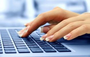 mains féminines tapant sur ordinateur portable, gros plan photo