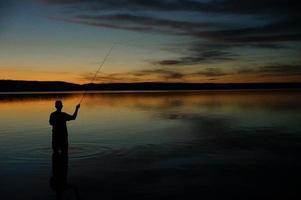 pêche à la mouche au coucher du soleil photo
