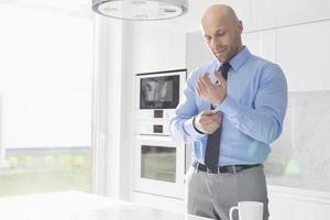 mi homme d'affaires adulte boutonner la manche à la maison photo