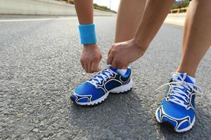 coureur de jeune femme attacher les lacets sur la route de la ville photo