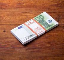 gros plan de 100 billets en euros sur fond de bois. photo