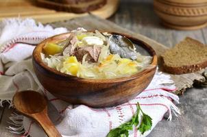 soupe de chou aigre rustique à l'oie dans un bol en bois. photo
