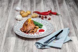 oie rôtie aux figues. assiette pleine de viande d'oie et photo