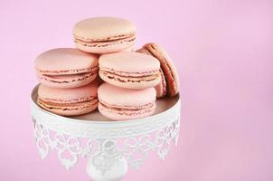 Macarons roses sur un stand de gâteau de style vintage blanc