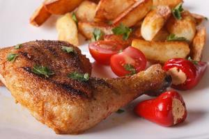 cuisses de poulet grillées, pommes de terre frites et macro de légumes.