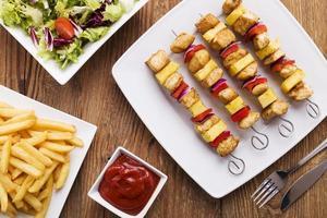 brochettes de poulet grillé avec ananas, poivrons et oignons servent photo