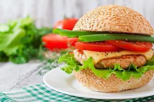 sandwich avec burger au poulet, tomates, fromage et laitue photo