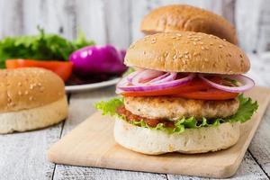 sandwich avec burger au poulet, tomates, oignons rouges et laitue