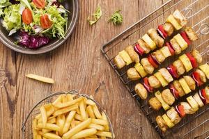 brochettes de poulet grillé avec ananas, poivrons et oignons servent