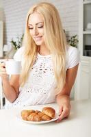 belle jeune femme blonde bénéficiant d'un croissant croustillant frais photo