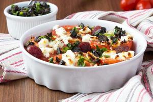 tomates cuites au fromage feta, saucisses fumées, herbes, olive