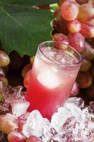 jus de raisin rose frais avec de la glace photo
