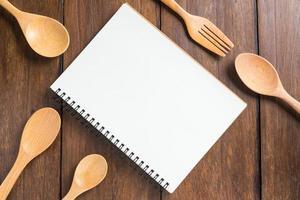 cahier de recettes, cuillère, fourchette sur fond de bois photo