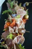 sélection de charcuterie comprenant salami, chorzio, jambon de parme et garniture de salade.