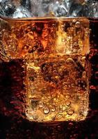 bulles dans le verre de cola avec de la glace.