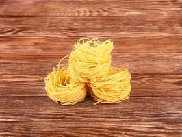 pâtes sur le fond en bois avec tomate, poivre de laitue, olive
