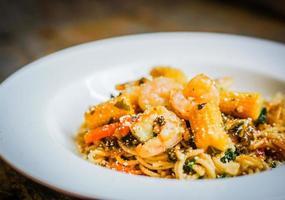 Pâtes italiennes aux crevettes et légumes sur fond de bois photo