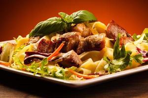 pâtes avec viande rôtie et légumes photo