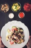 salade de fruits de mer à la main avec vue de dessus des ingrédients flous photo