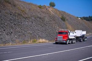 semi camion rouge et deux remorques sur la voie haute