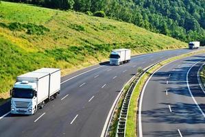 Autoroute avec trois camions blancs venant en sens inverse dans un paysage boisé