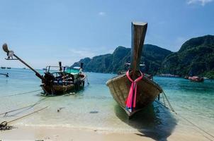 bateaux à longue queue sur la plage d'eau turquoise photo