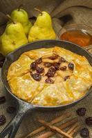 Tarte chaude aux poires et cerises dans une poêle en fonte