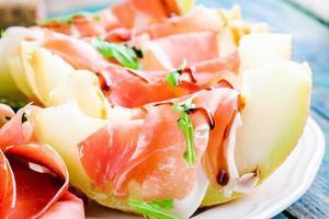 melon, à, tranches, de, prosciutto, roquette, et, sauce balsamique, closeup photo