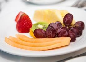 assiette de fruits en tranches avec des raisins