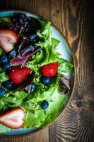 salade verte aux fruits rouges sur fond de bois photo