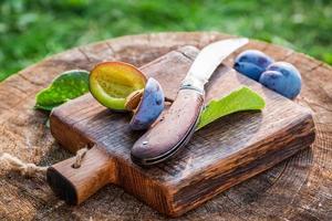 prunes fraîches sur planche de bois photo