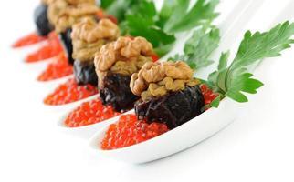pruneaux farcis de noix de pâté de foie dans un caviar rouge photo