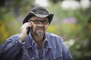 homme au chapeau, parler au téléphone portable photo