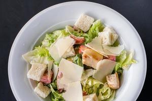 salade César au poulet et légumes verts sur table en bois