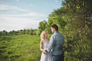couple nouvellement marié dans le bois autour d'un arbre photo