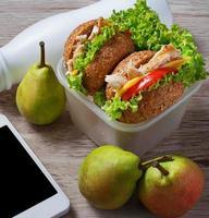 boîte à lunch avec hamburgers, poires et yaourt